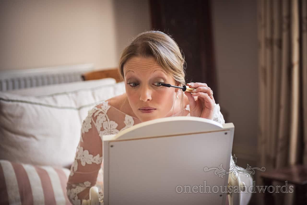 Bride applies wedding makeup in mirror on wedding morning in Sherborne