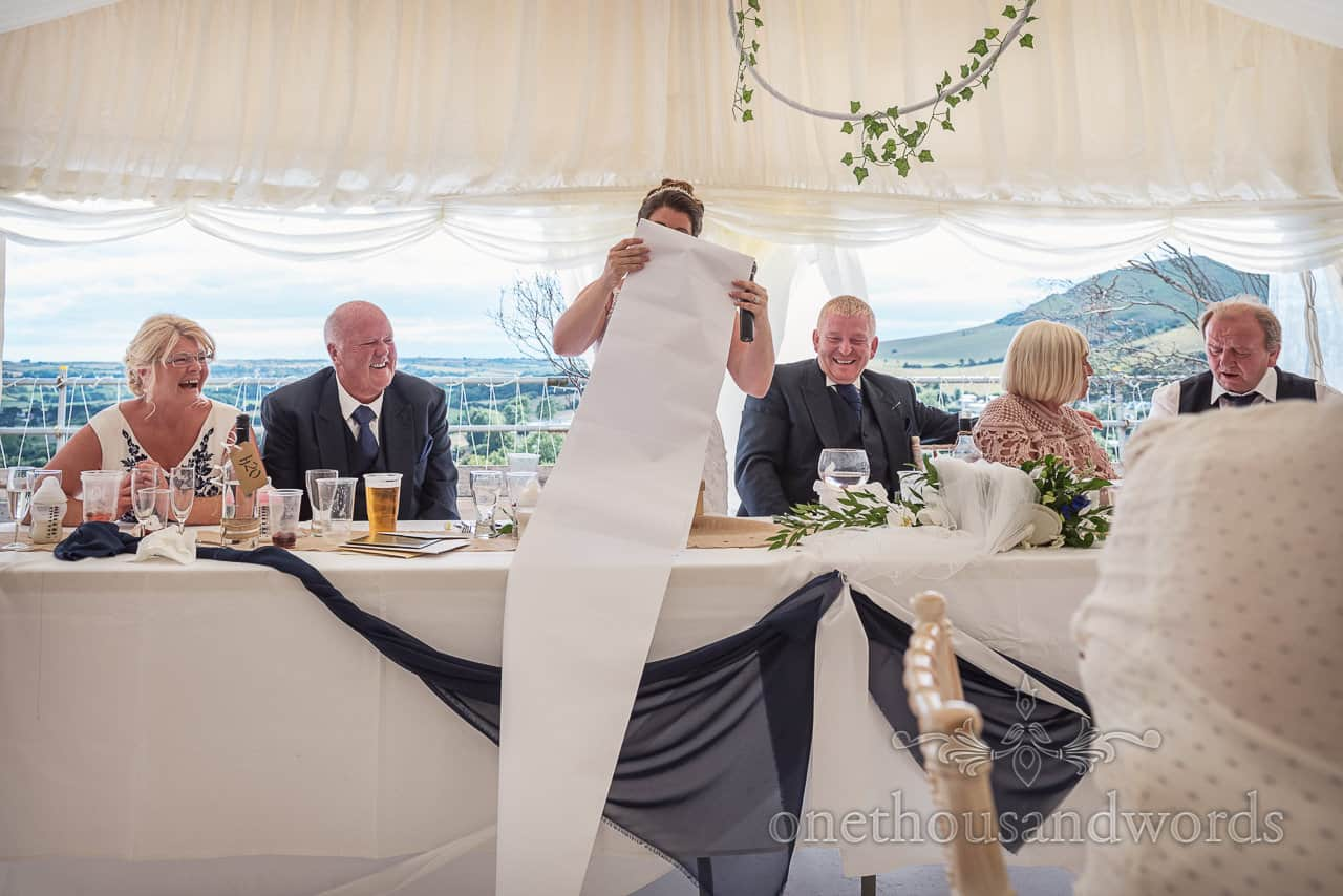 Bride makes wedding speech with long paper roll of notes as top table wedding guests laugh