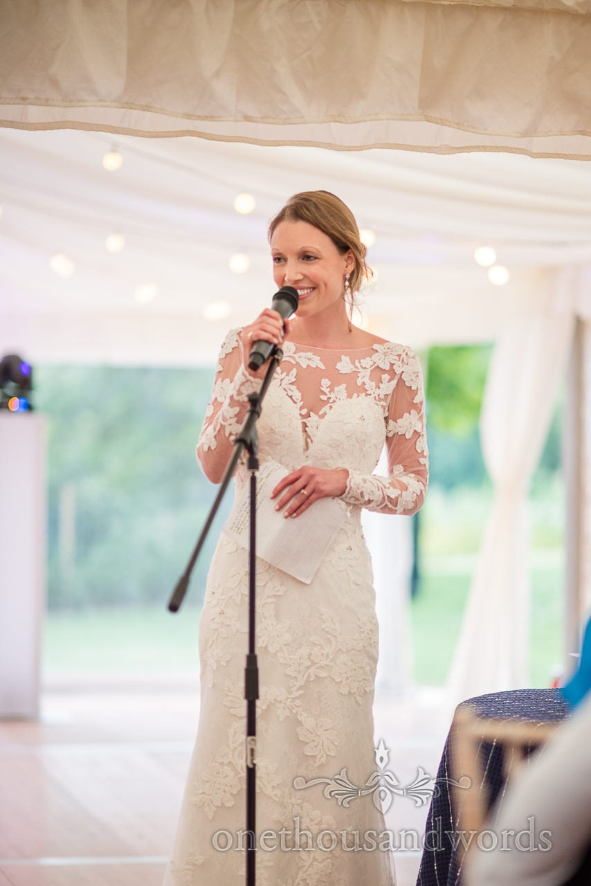 Beautiful bride makes wedding speech with microphone at Sherborne Castle wedding marquee reception photograph