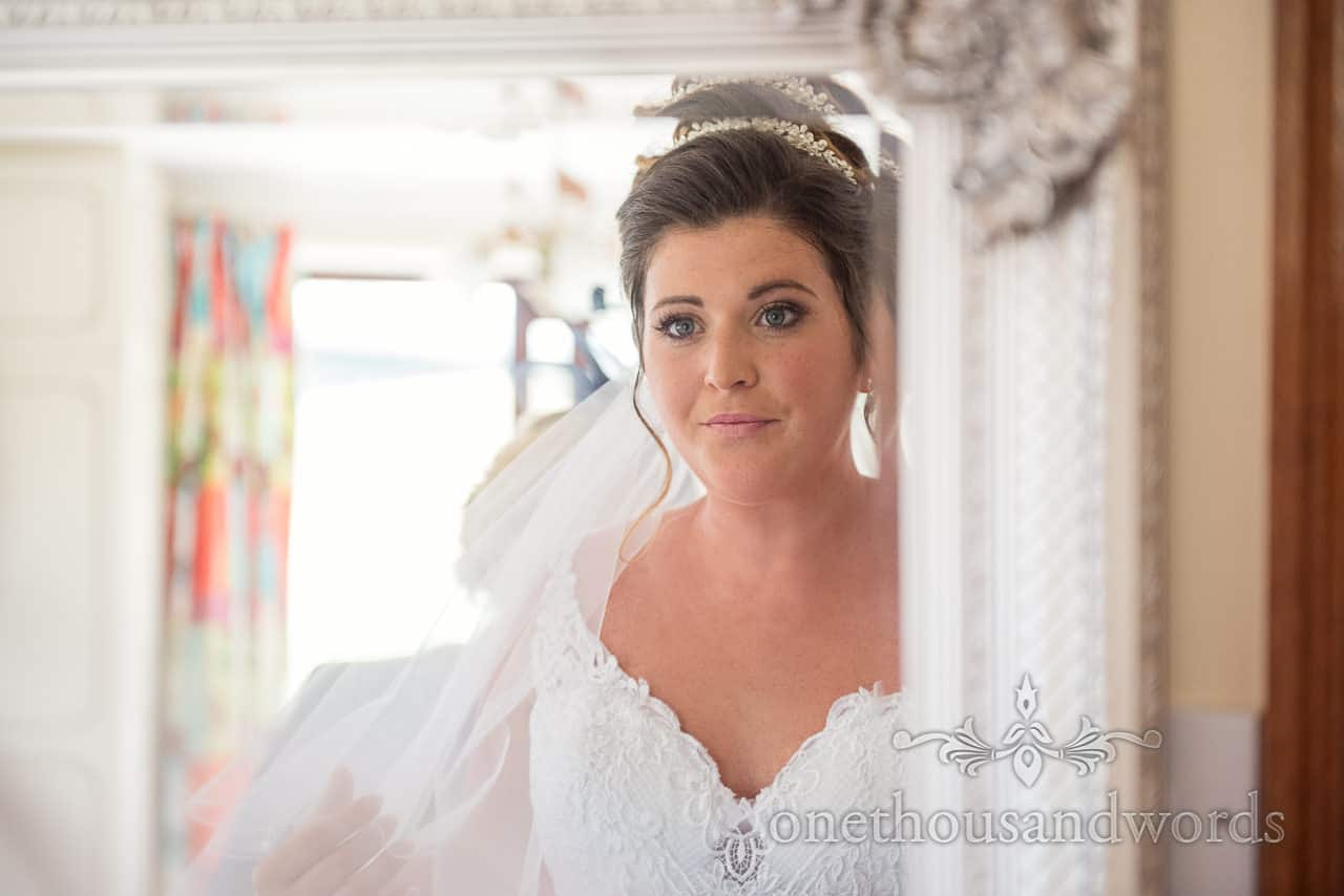 Bride in white detailed wedding dress, veil and diamanté hair band looks in mirror on wedding morning