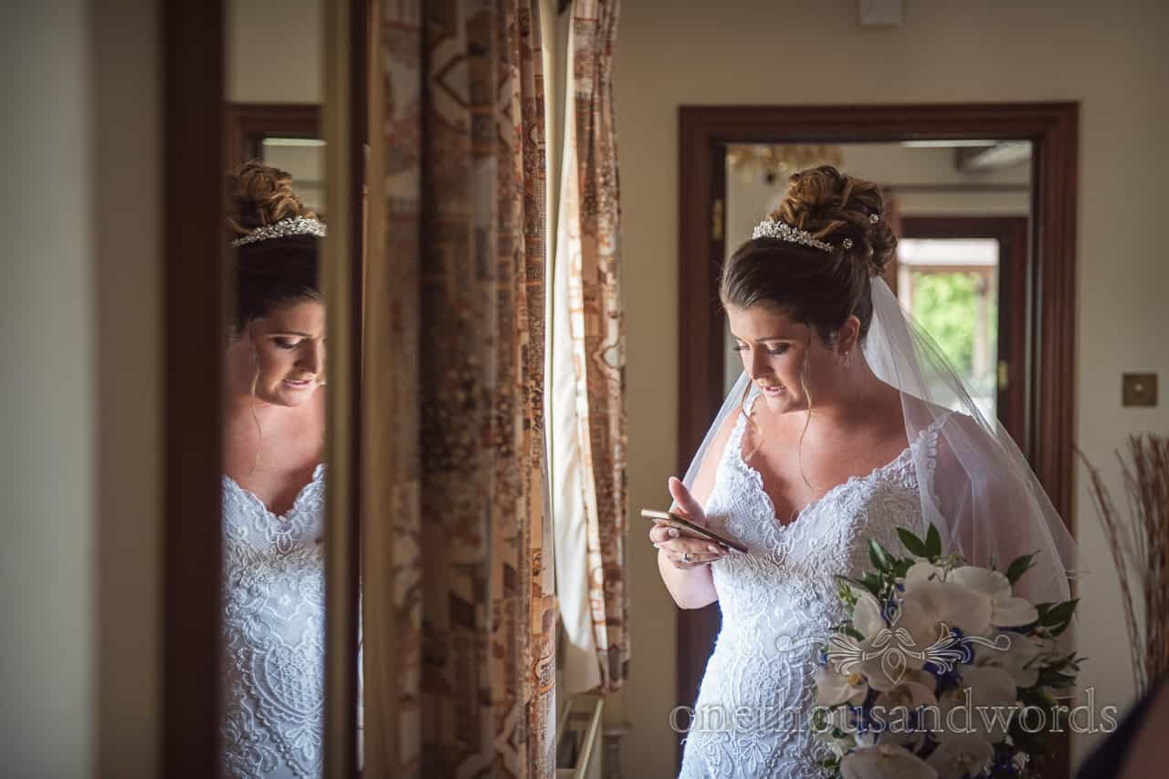 Bride in white wedding dress checks mobile phone in window next to mirror on wedding morning before leaving for church