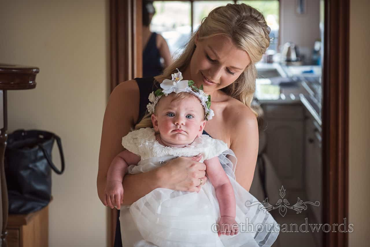 Bride's baby daughter in white flower girl dress and floral headband with bridesmaid on wedding morning