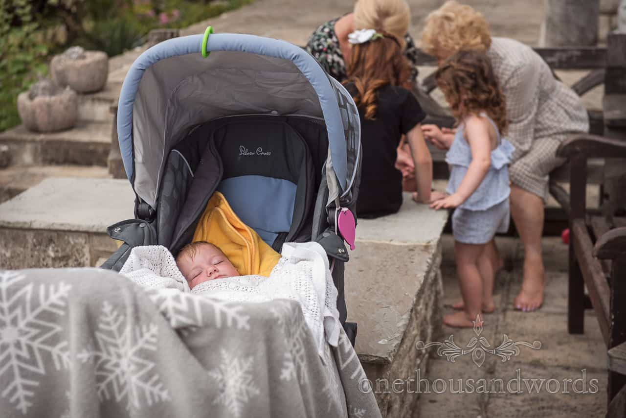 Bride's baby sleeps in pram as family paint nails in the background on wedding morning photograph