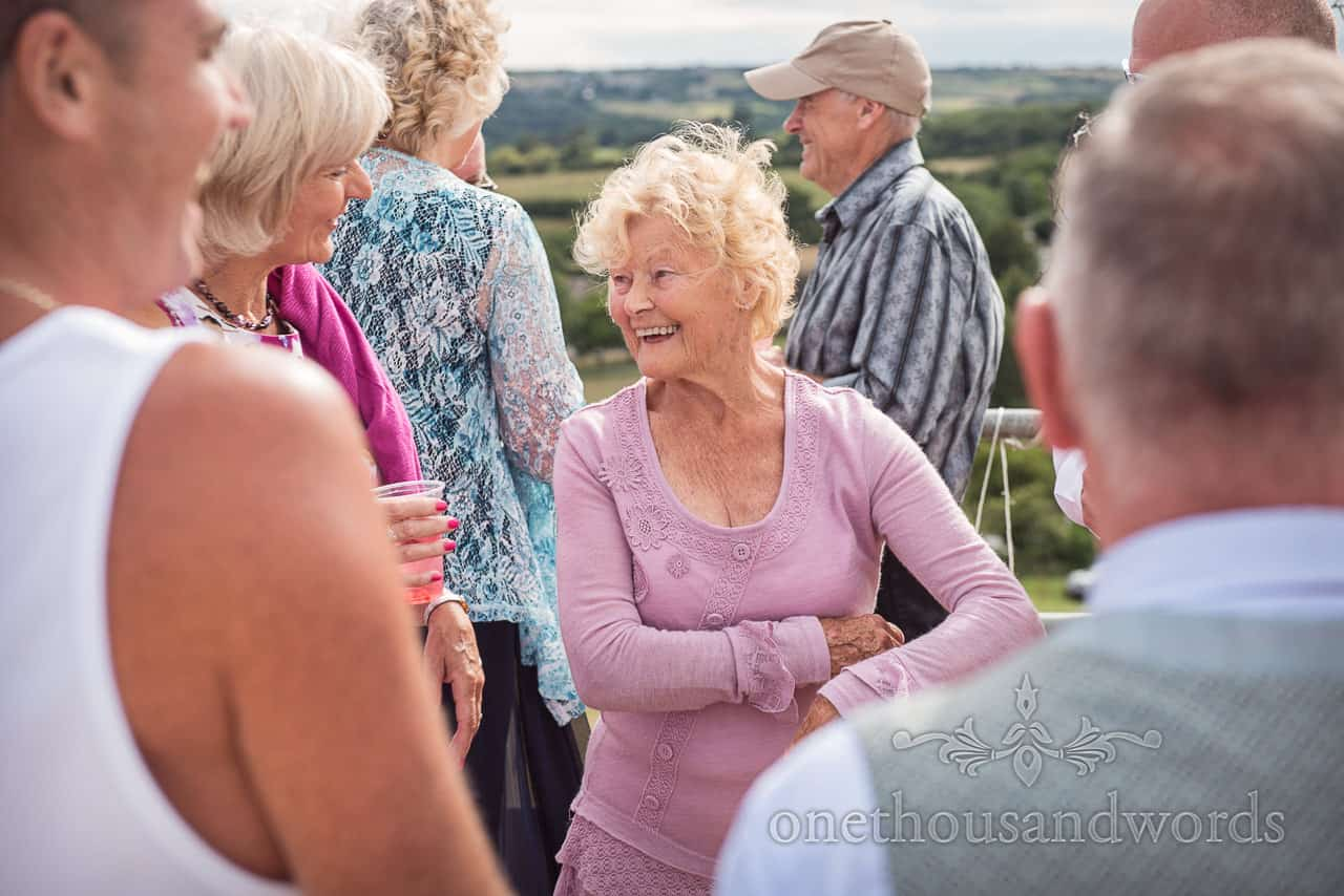 Bride's grandmother laughing at wedding drinks reception with countryside in background