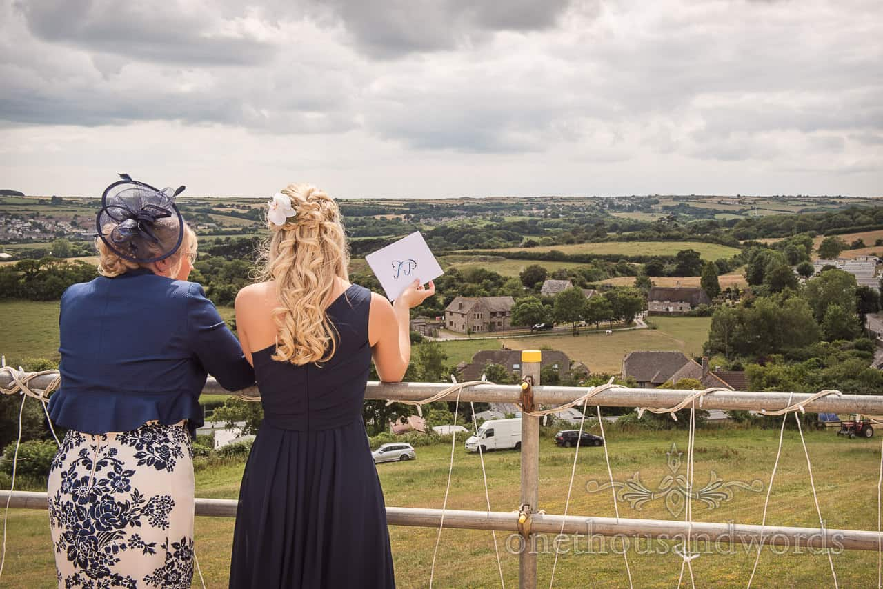 Bride's sister and mother looking at view over Swanage from wedding marquee scaffold terrace