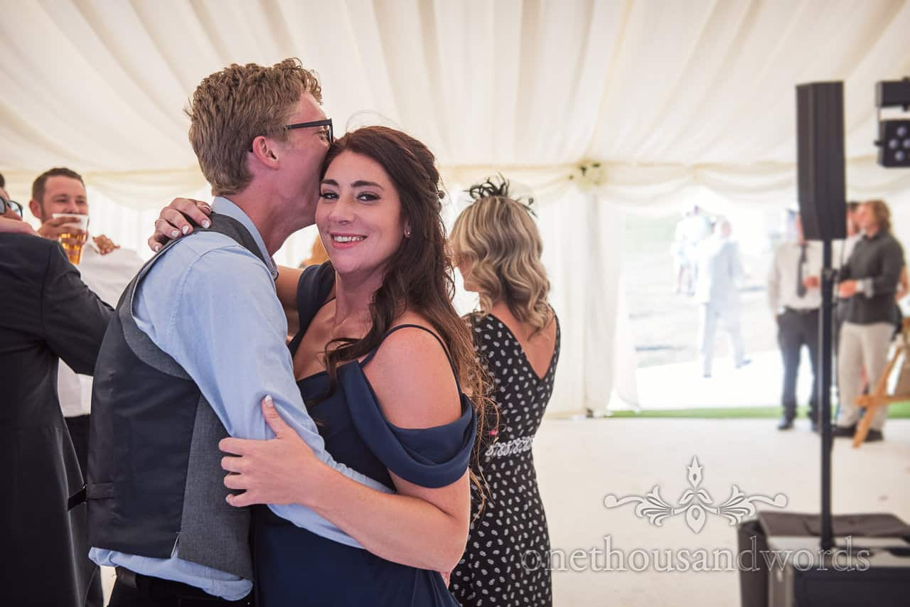 Bridesmaid looks at camera as she embraces partner during wedding dancing in marquee