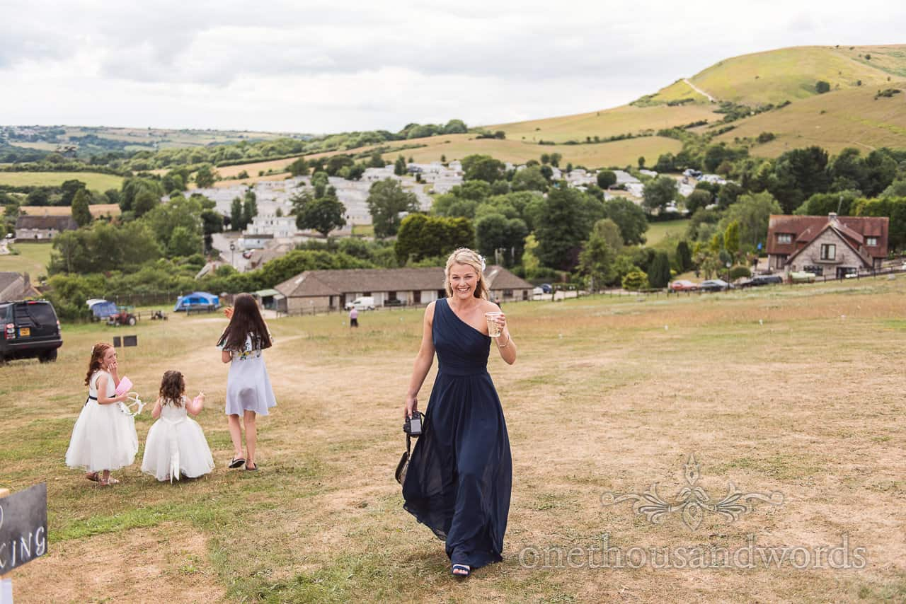 Bridesmaid in navy blue dress walks up hill towards wedding overlooking countryside hills with drink in hand