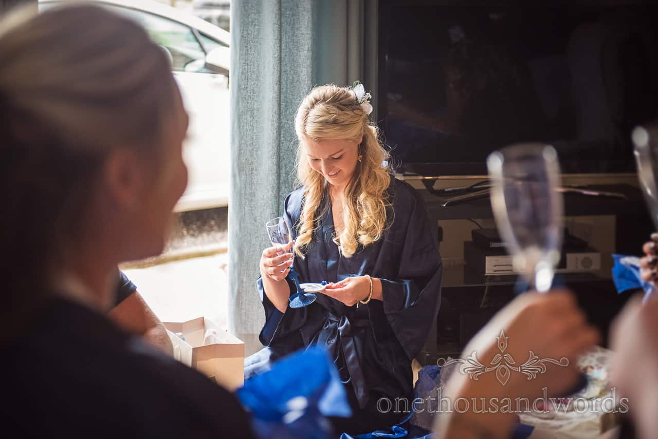 Bridesmaid in dark blue silk dressing gown receives wedding morning champagne glass gift from bride