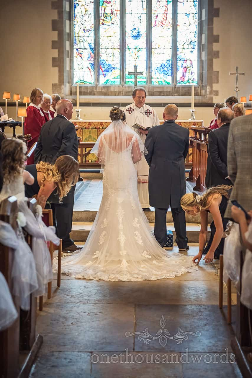 Bridesmaids adjust the bride's wedding dress train in front of altar at church wedding ceremony in Swanage, Dorset