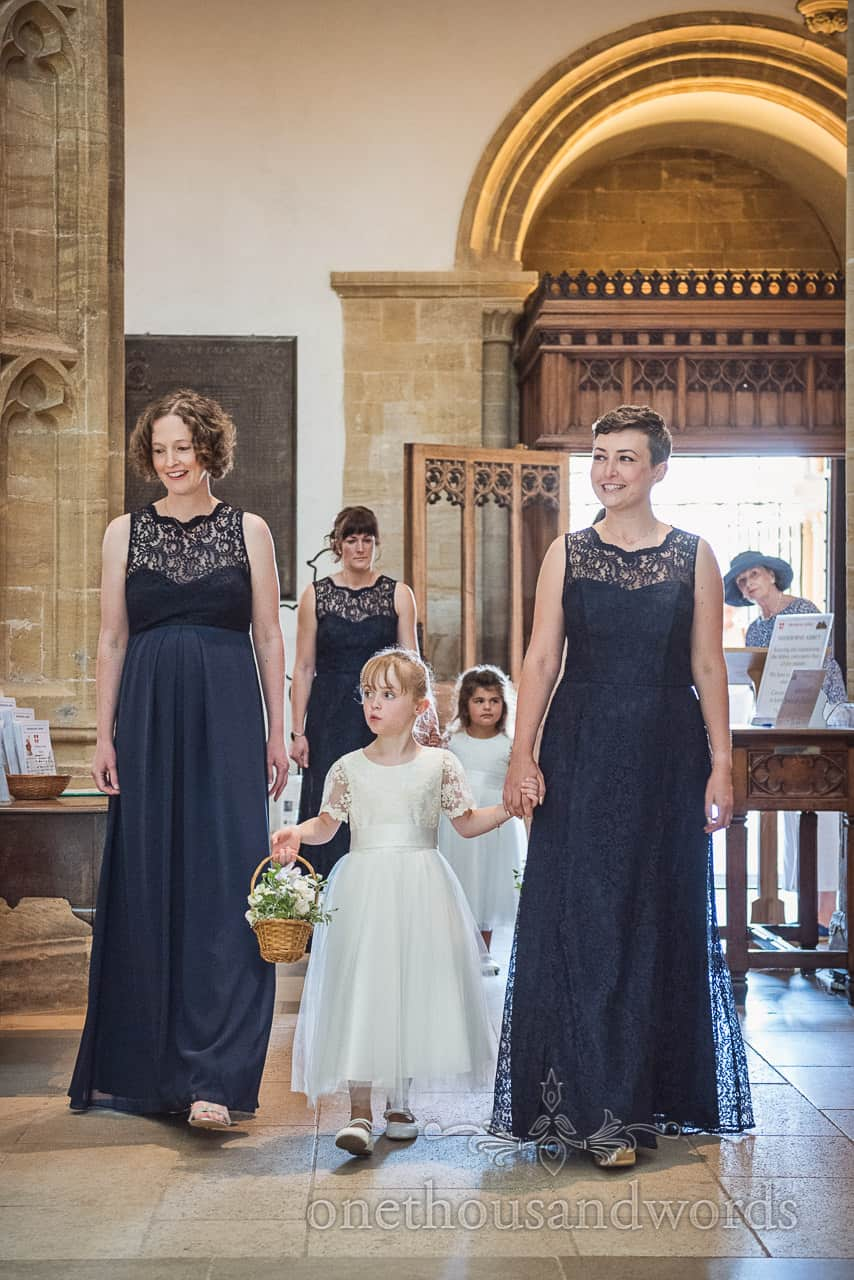 Bridesmaids and Flower girls arrive to walk up the aisle at Sherborne Abbey wedding venue in Dorset