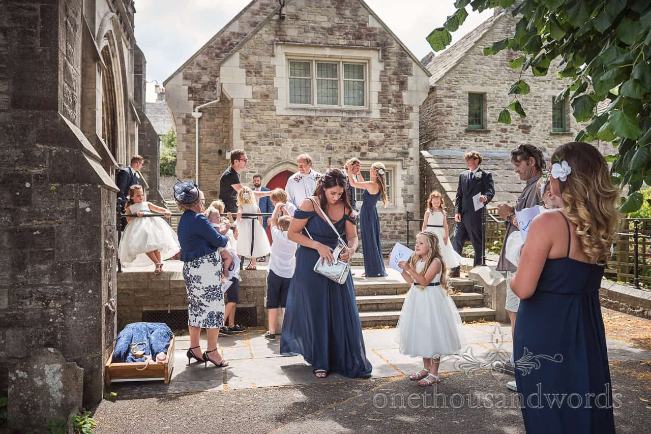 Documentary wedding photograph of bridesmaids with flower girls and page boys and groomsmen outside Swanage Church