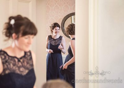 Documentary wedding photograph of happy bridesmaids wearing navy blue dresses preparing for wedding morning in family house