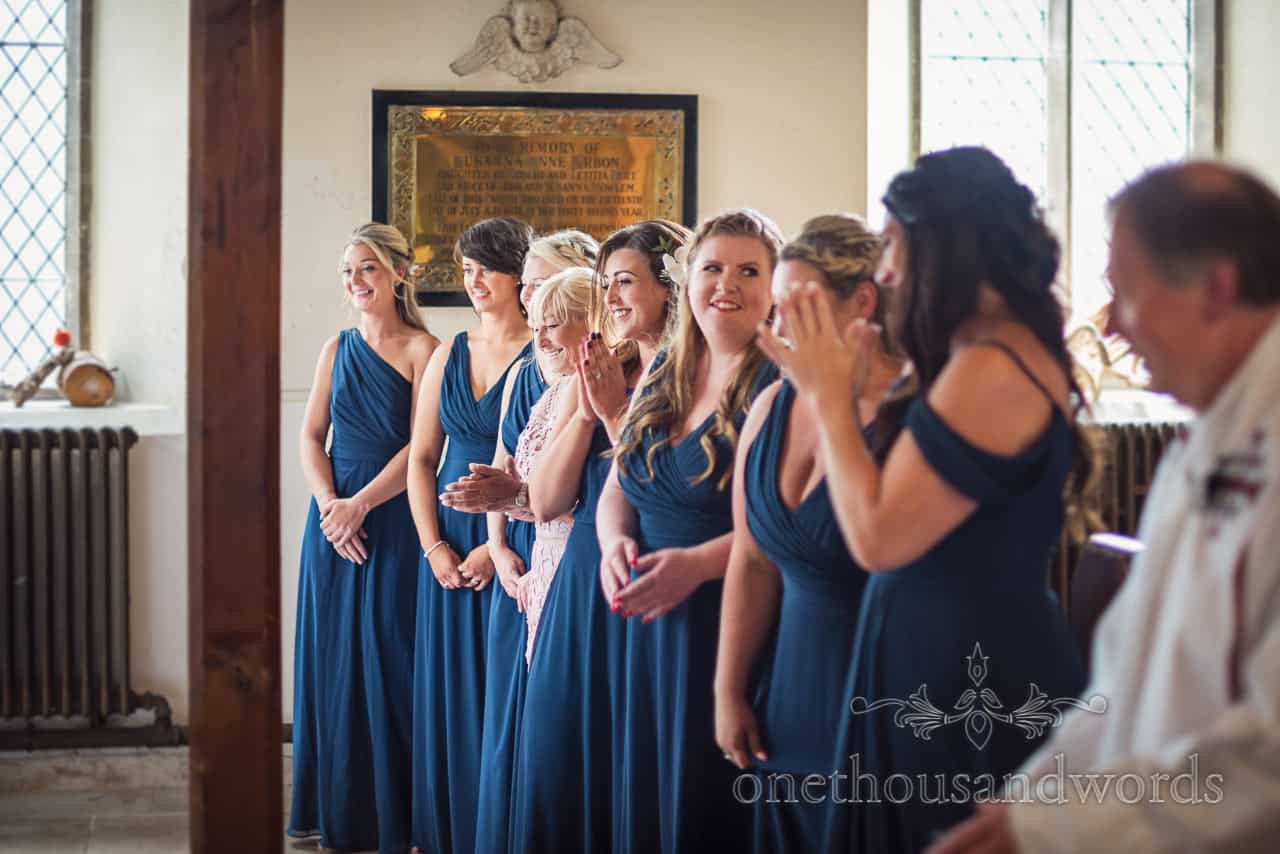 Bridesmaids in navy blue dresses smile and clap as they watch the bride signing marriage register in church