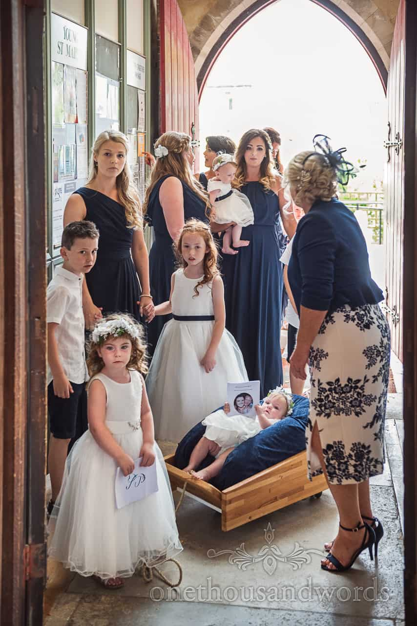 Bridesmaids in deep blue dresses with flower girls and page boys and baby trailer waiting at church doorway
