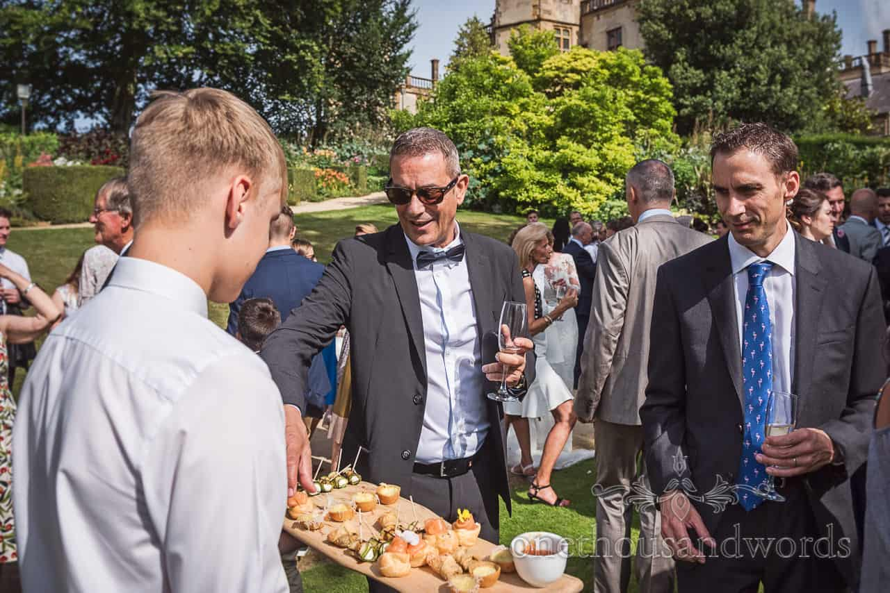 Wedding guests enjoy drinks and canapés at Sherborne Castle orangery wedding drinks reception in the gardens
