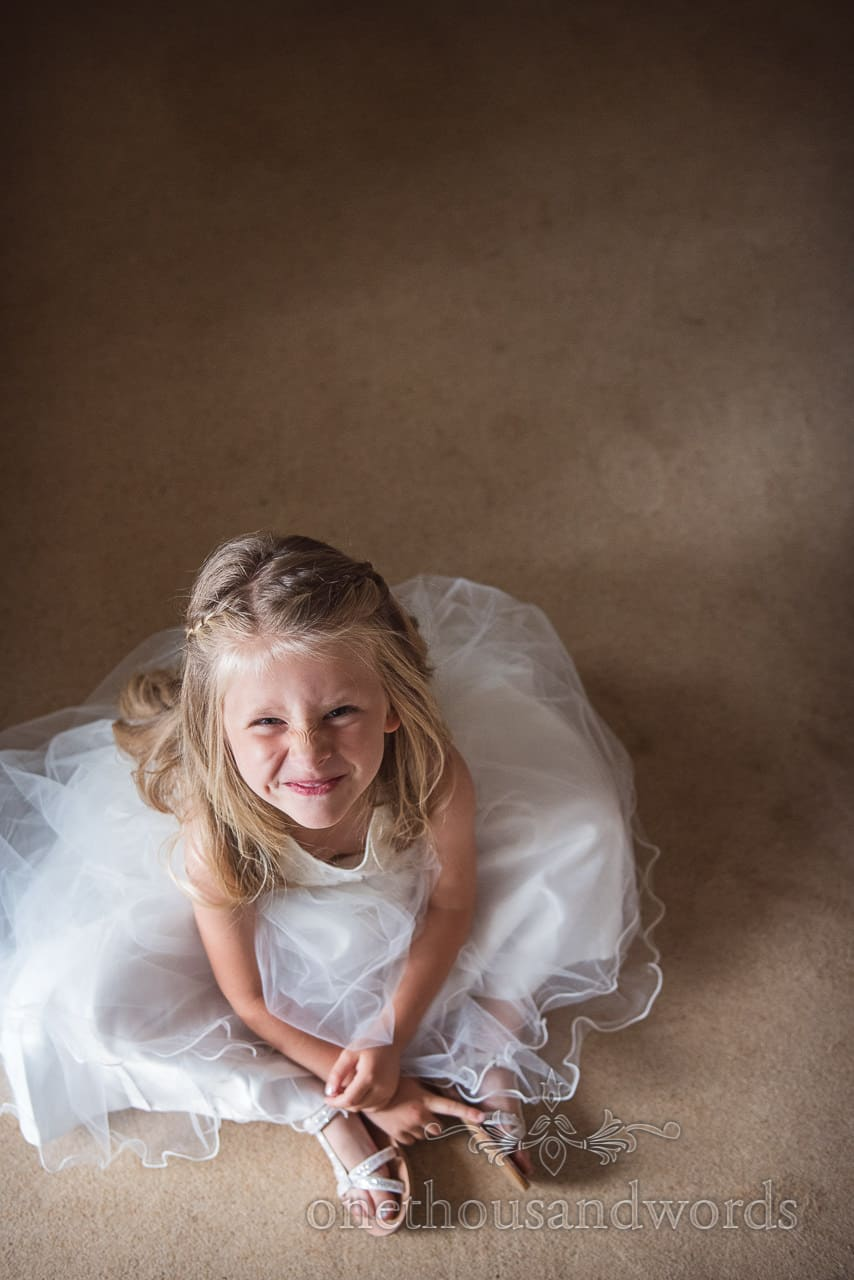 Cheeky blonde flower girl in white dress scrunches up her face on wedding morning photograph