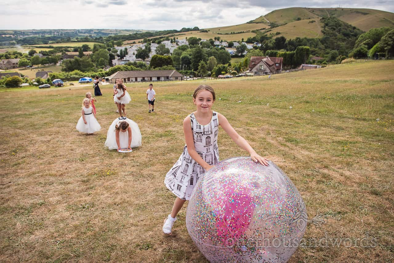 Children and flower girls at wedding roll large inflatable ball up Dorset countryside hill field