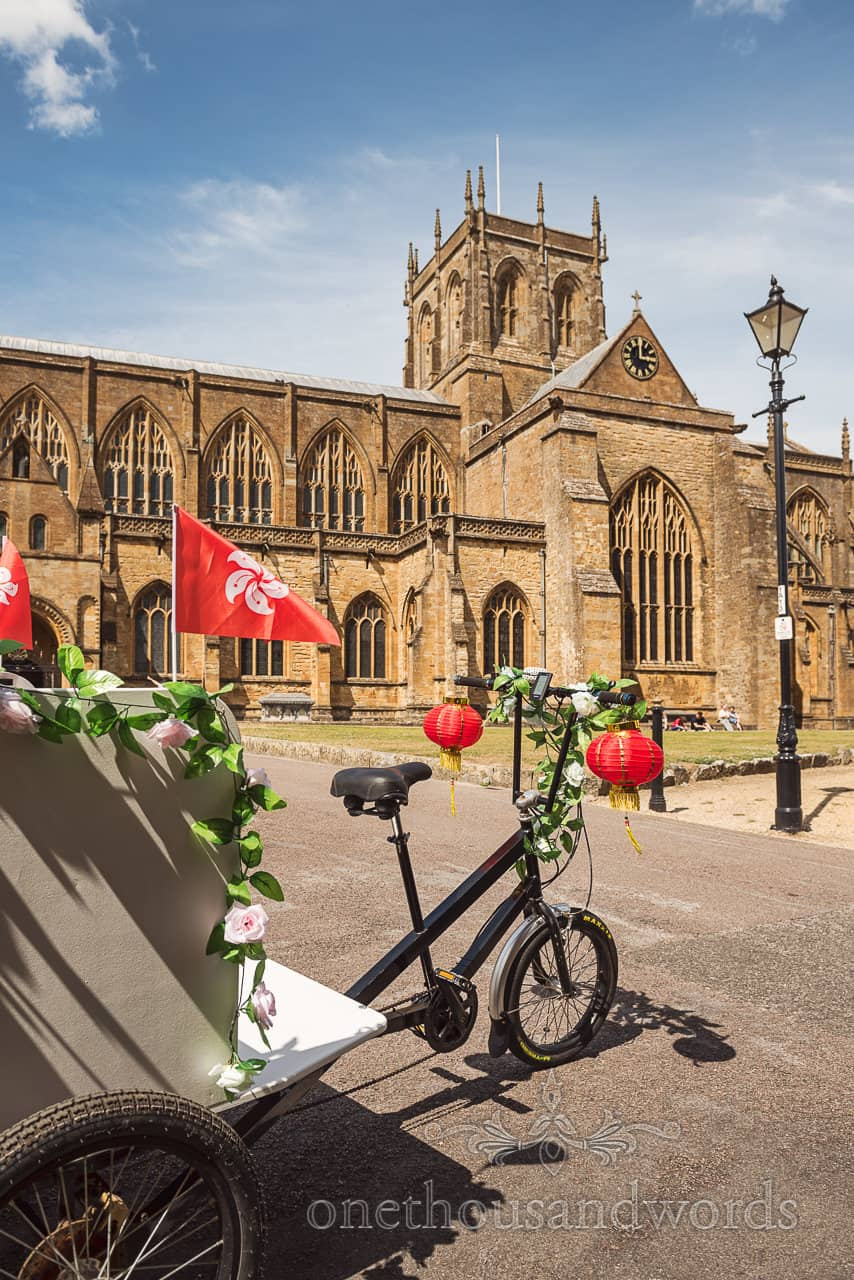 Chinese decorated wedding e-trike sits outside Sherborne Abbey wedding venue in Dorset on a summer's wedding day