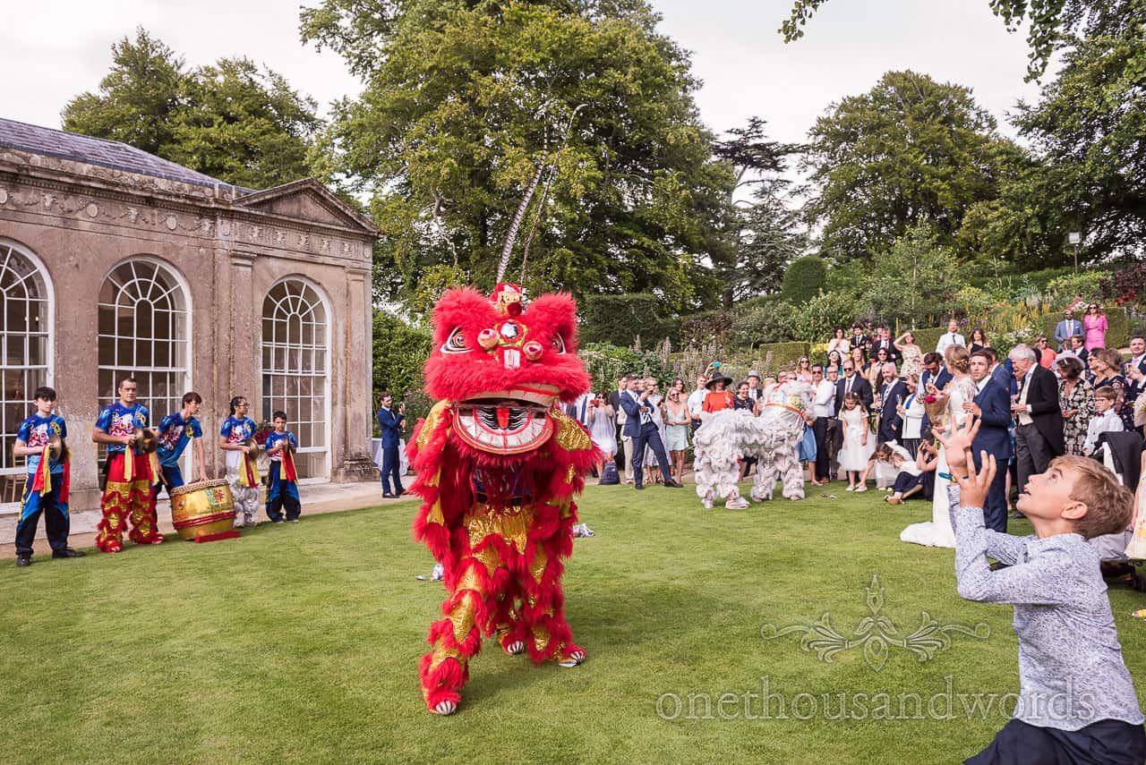 Traditional Chinese dragon dance at Sherborne Castle wedding drinks reception in Dorset