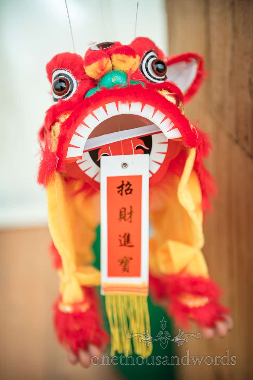 Wedding detail photograph of Chinese dragon paper puppet used as wooden wedding bar decoration