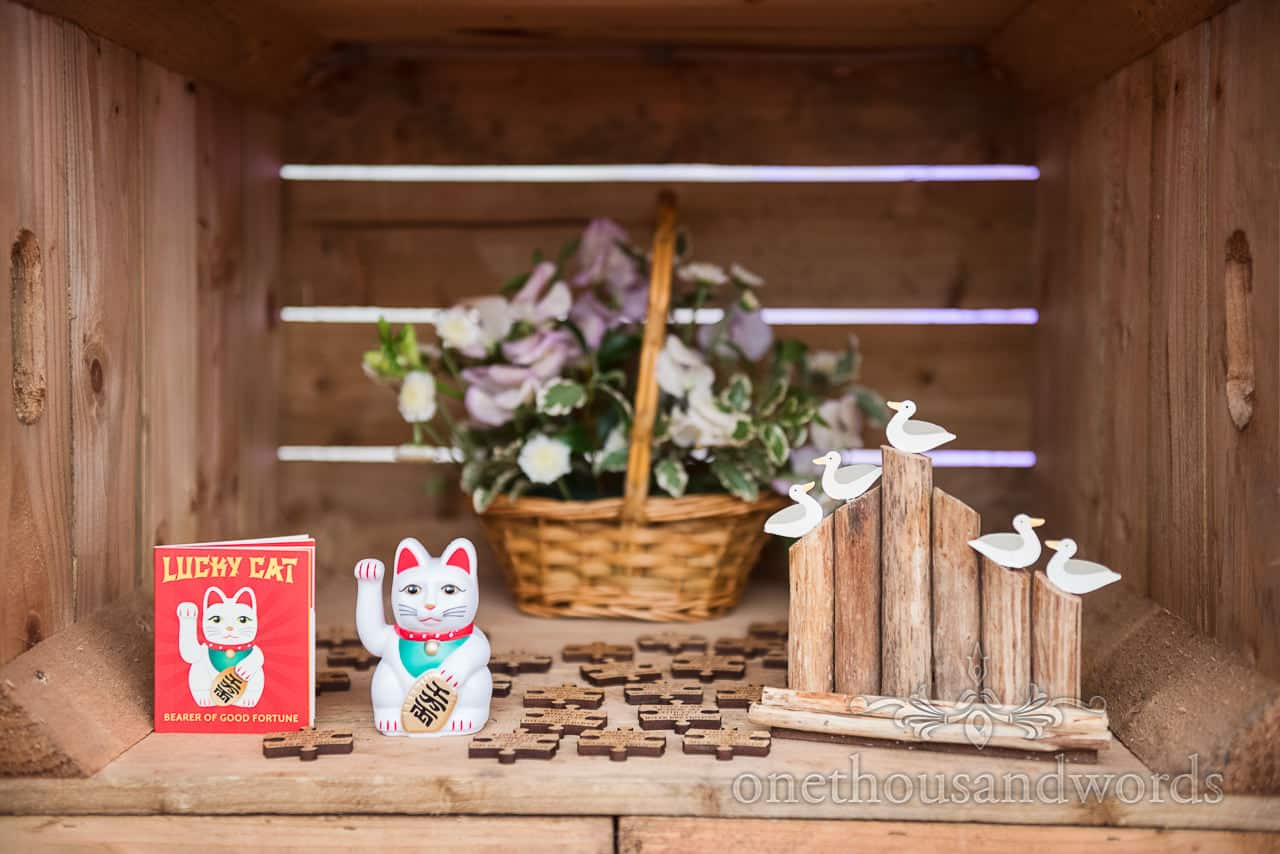 Detail wedding photograph of Chinese lucky cat, sea gulls, jig saw pieces, and wicker basket of flowers in wooden crate