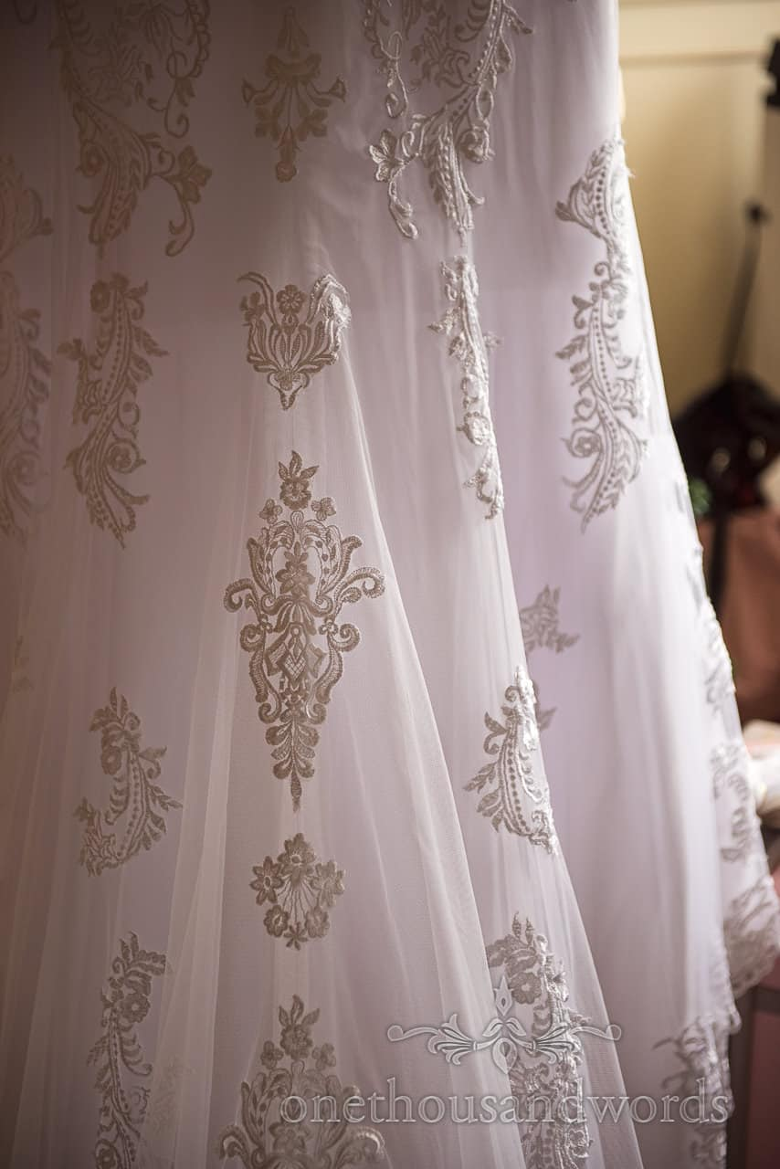 Close up detail wedding photograph of white wedding dress lace pattern