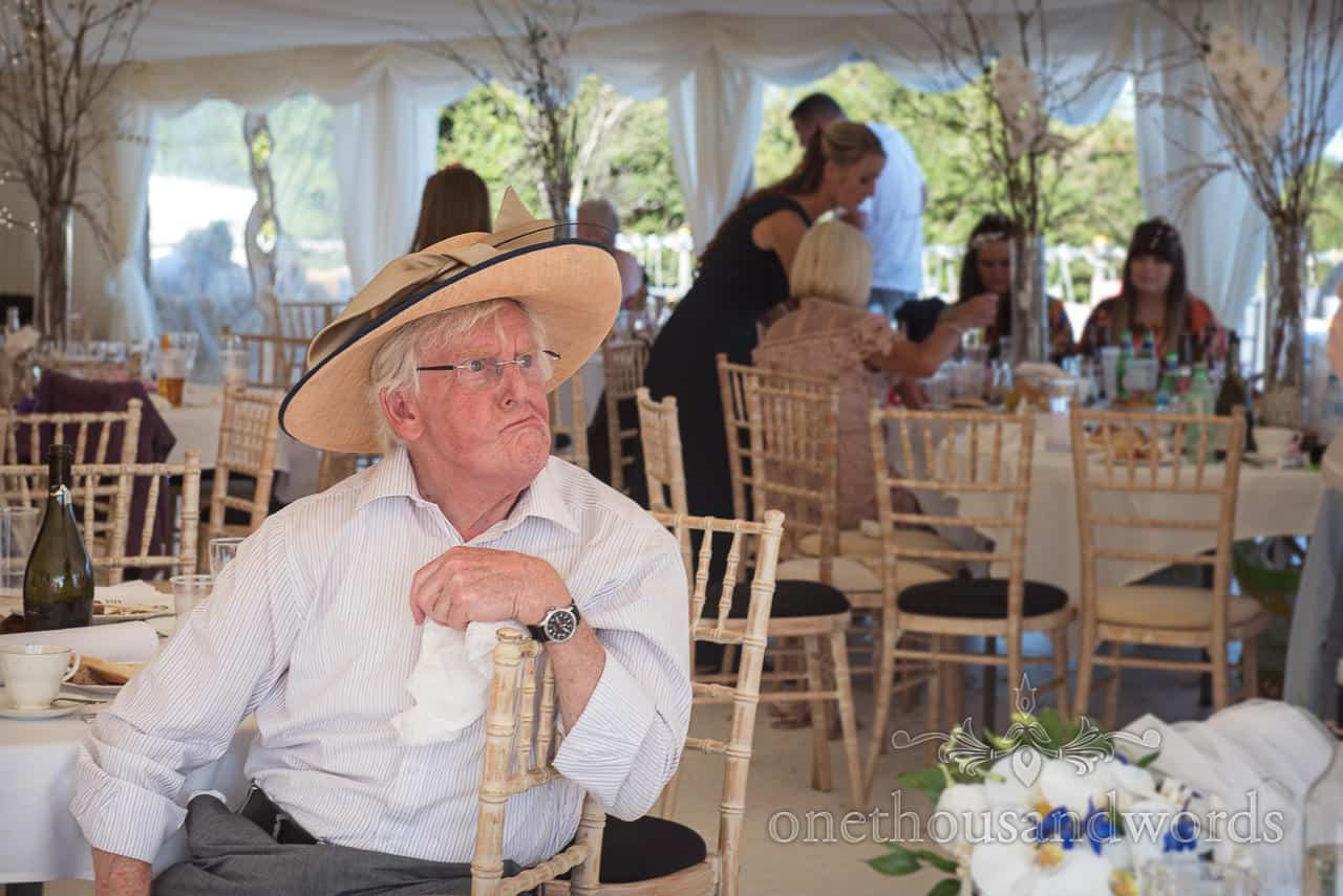 Comical male wedding guest pulls funny face as we wears a ladies hat in wedding marquee