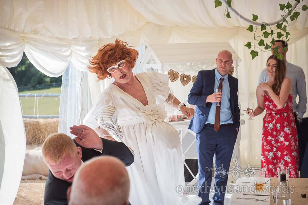 Drag act bride in wedding dress beats groom with handbag whilst singing at wedding marquee watched by guests
