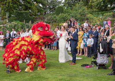 Traditional Chinese dragon dance with bride and groom in gardens from Sherborne Castle wedding photographs