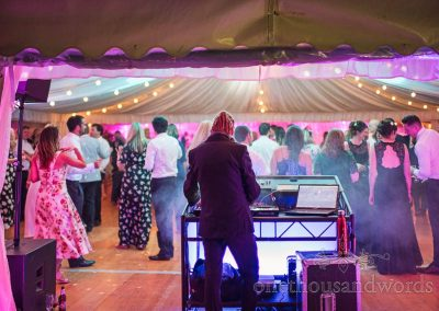 Dreadlocks wedding DJ Iggy in suit mixing music at Sherborne Castle wedding marquee evening dancefloor