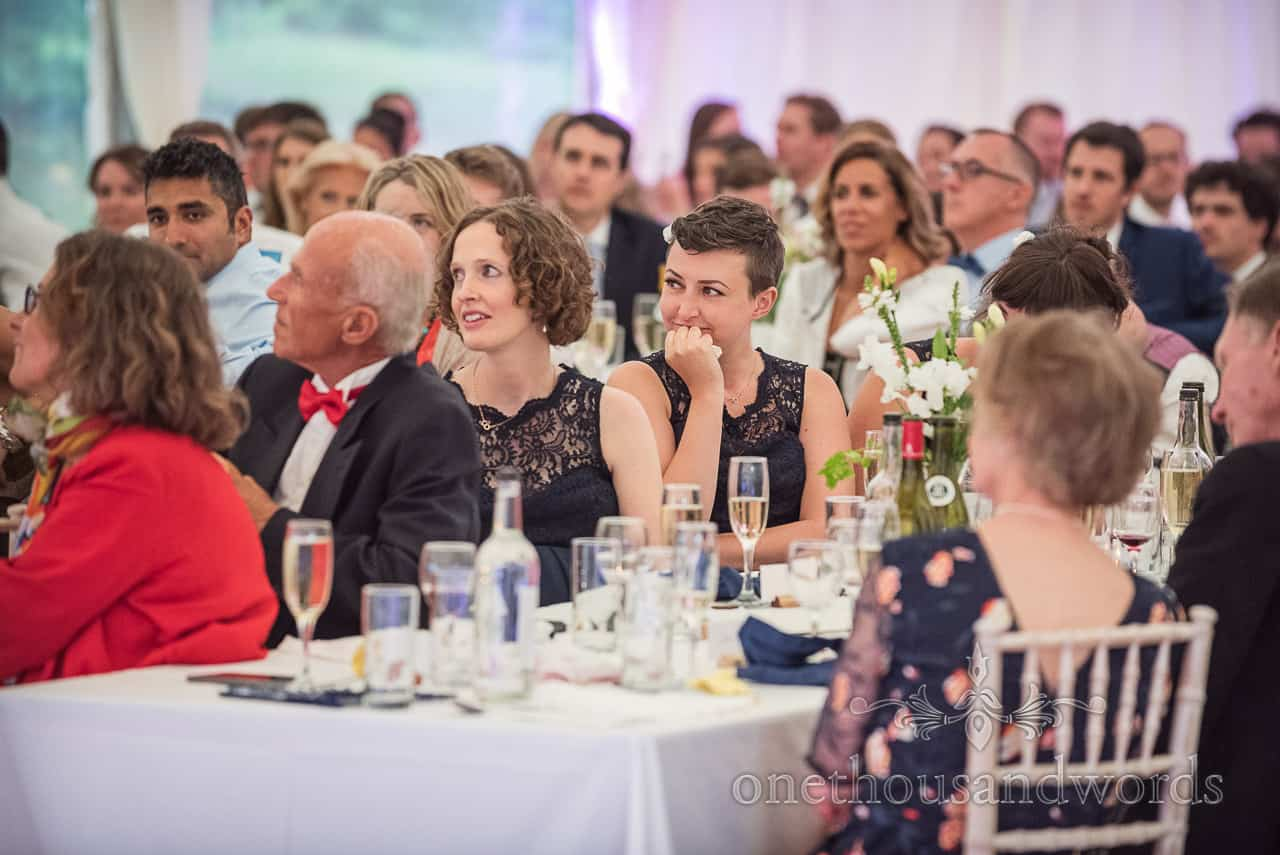 Emotional bridesmaid tears up as she listens to the wedding speeches in white wedding marquee at Sherborne Castle