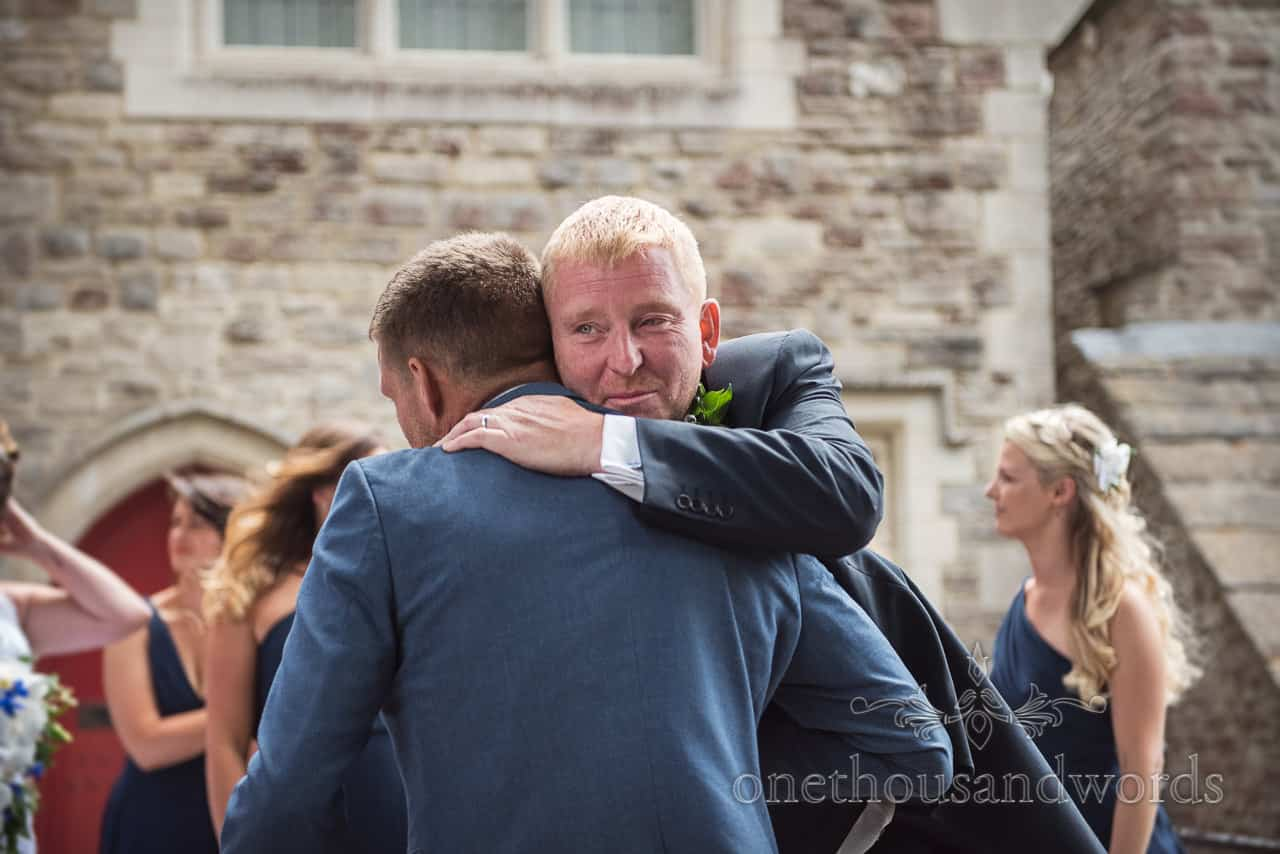 Emotional groom hugs wedding guests outside church after wedding ceremony
