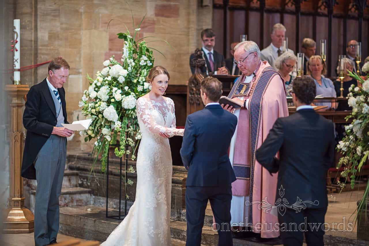 Bride and groom exchange wedding vows at Sherborne Abbey wedding ceremony watched by choir