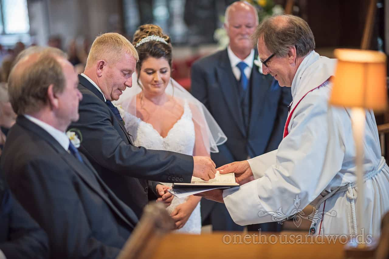 Exchange of wedding rings photograph as groom takes the ring from vicar in church wedding ceremony