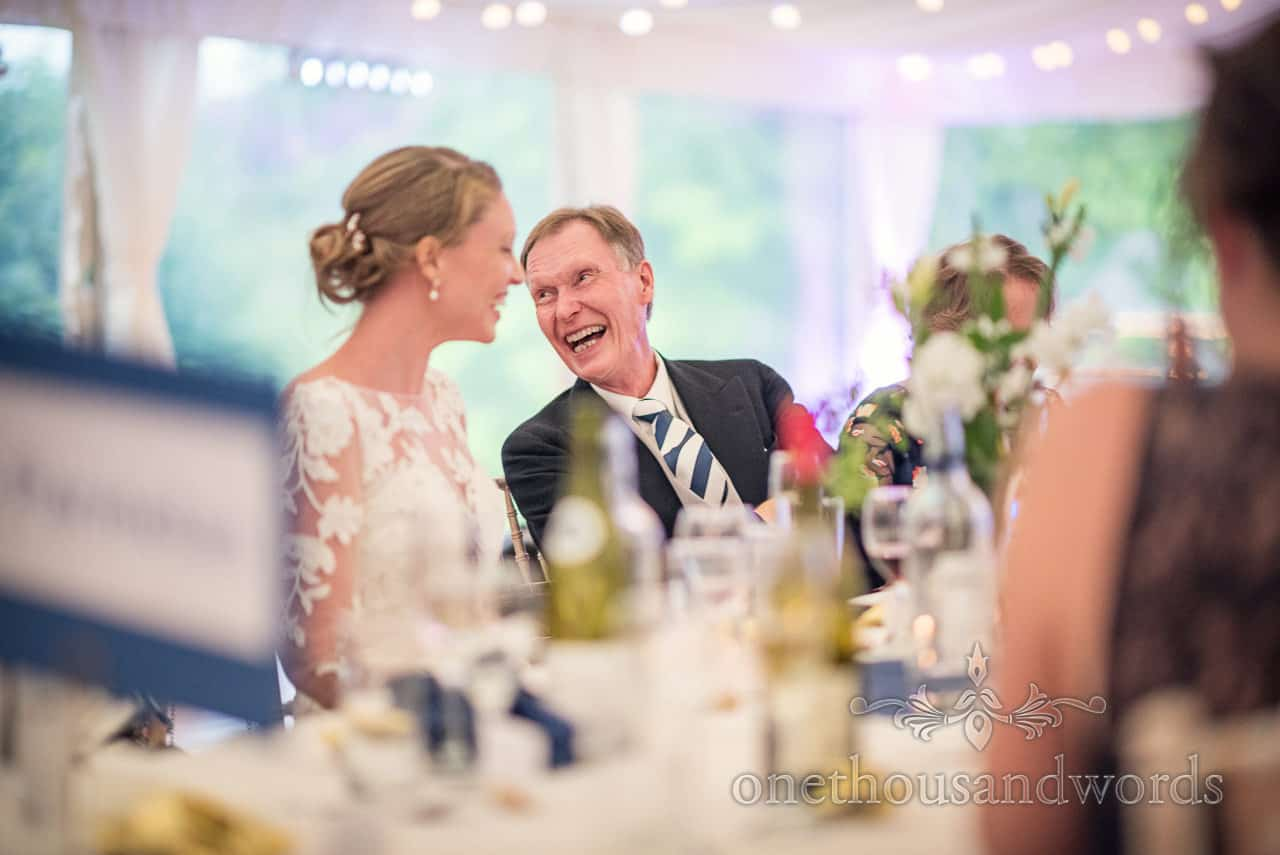 Father of the bride sat on top table laughing over his shoulder during wedding speeches at marquee wedding breakfast