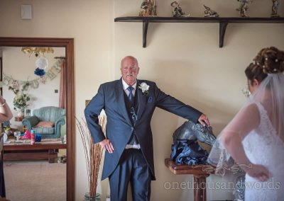Father of the bride in three piece navy morning tailcoat leans on sculpture waiting to leave family home on wedding morning in Dorset