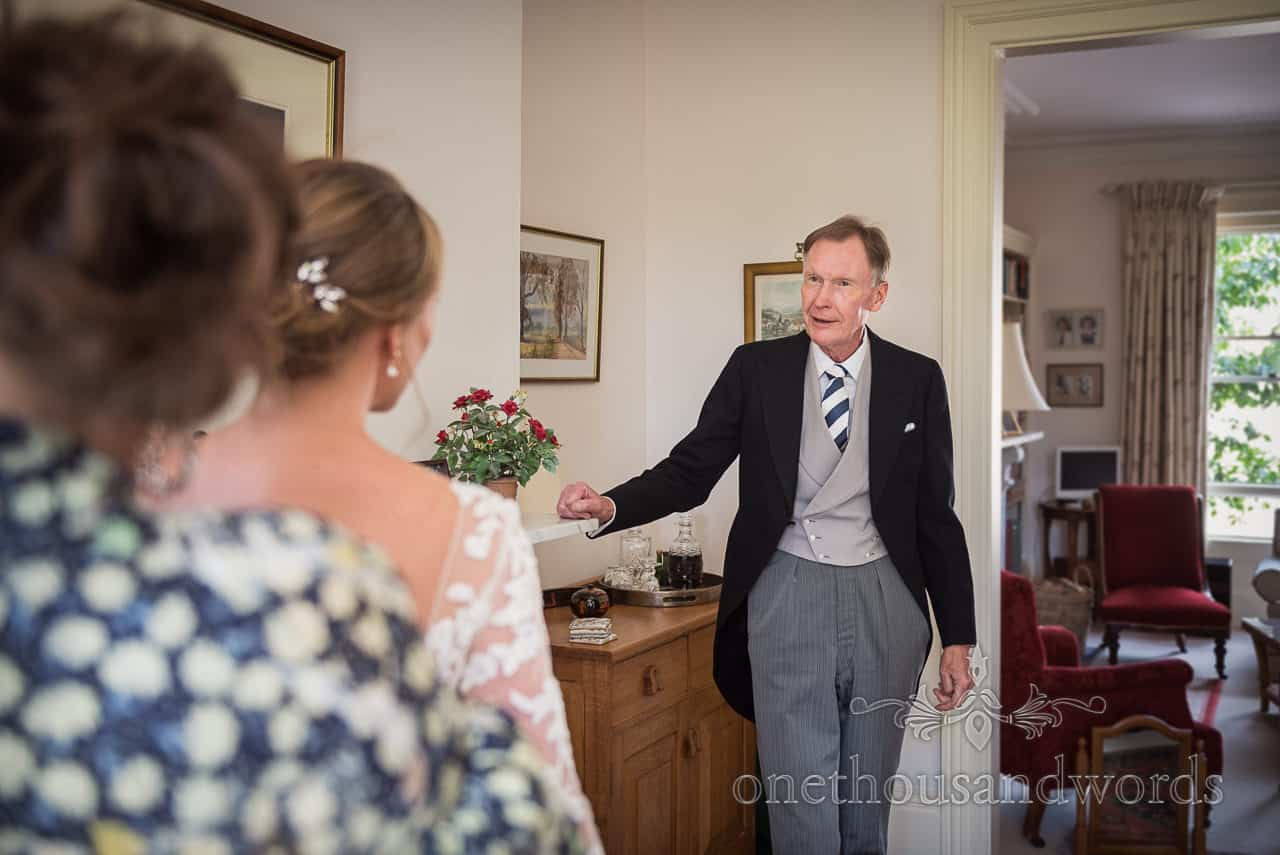 Father of the bride wearing morning suit chats to bride during wedding morning preparations at family home in Sherborne
