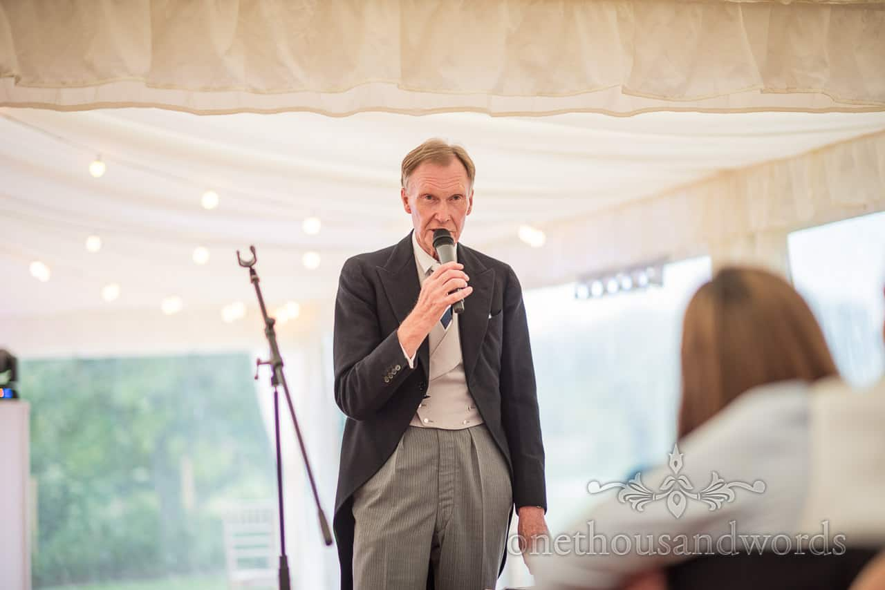 Father of the bride wearing black morning tail coat and grey trousers makes wedding speech with microphone in marquee