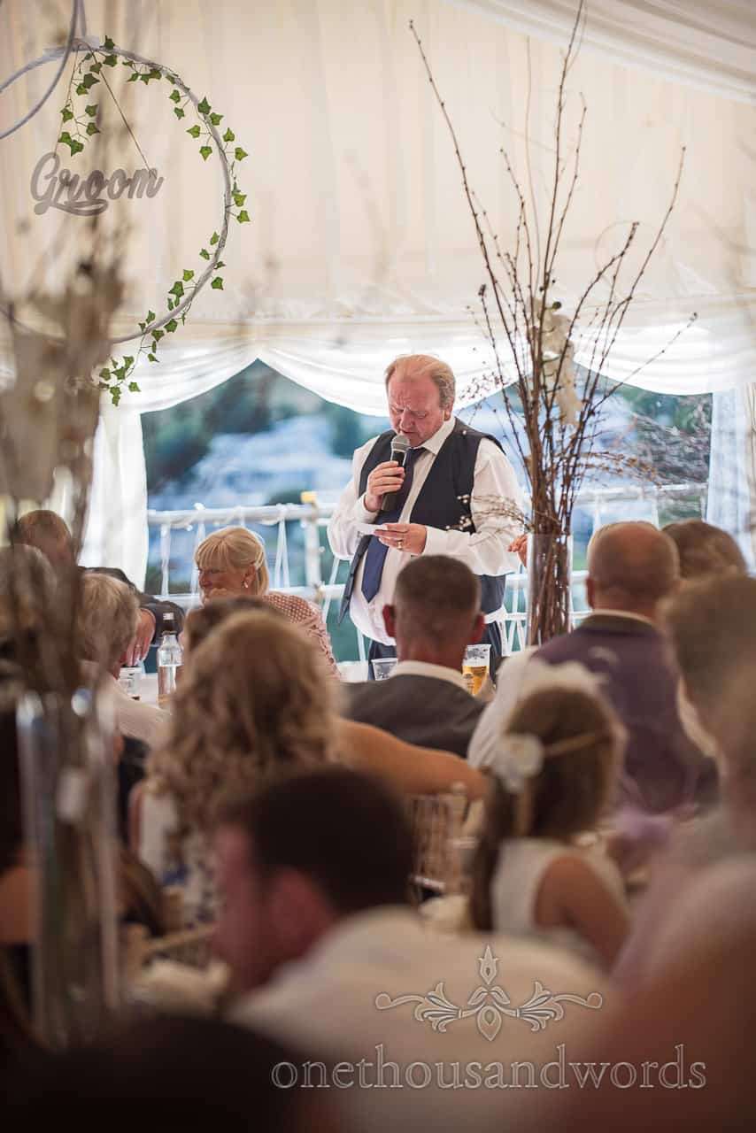Father of the groom makes wedding speech looking down at his notes in wedding marquee