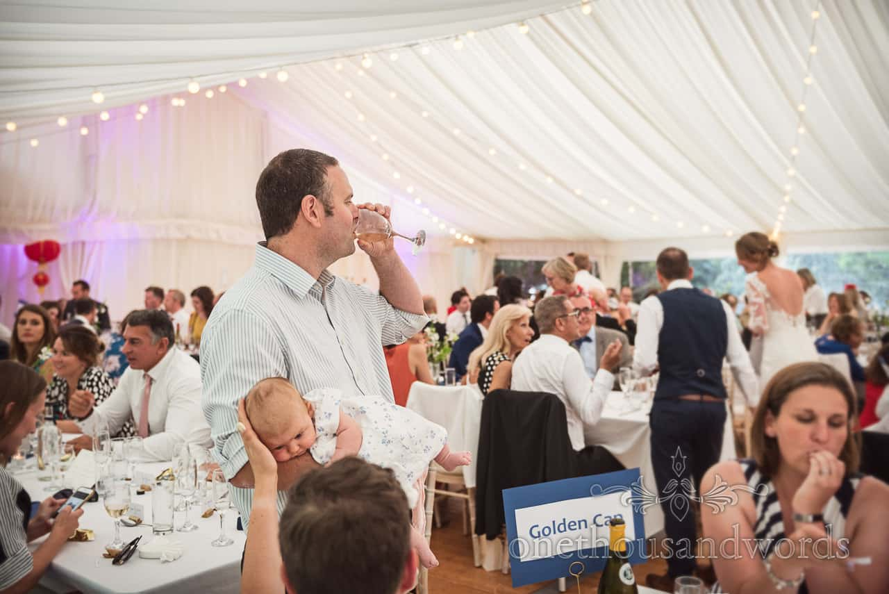 Documentary wedding photo of father holding baby whilst drinking glass of wine at Sherborne Castle wedding breakfast marquee