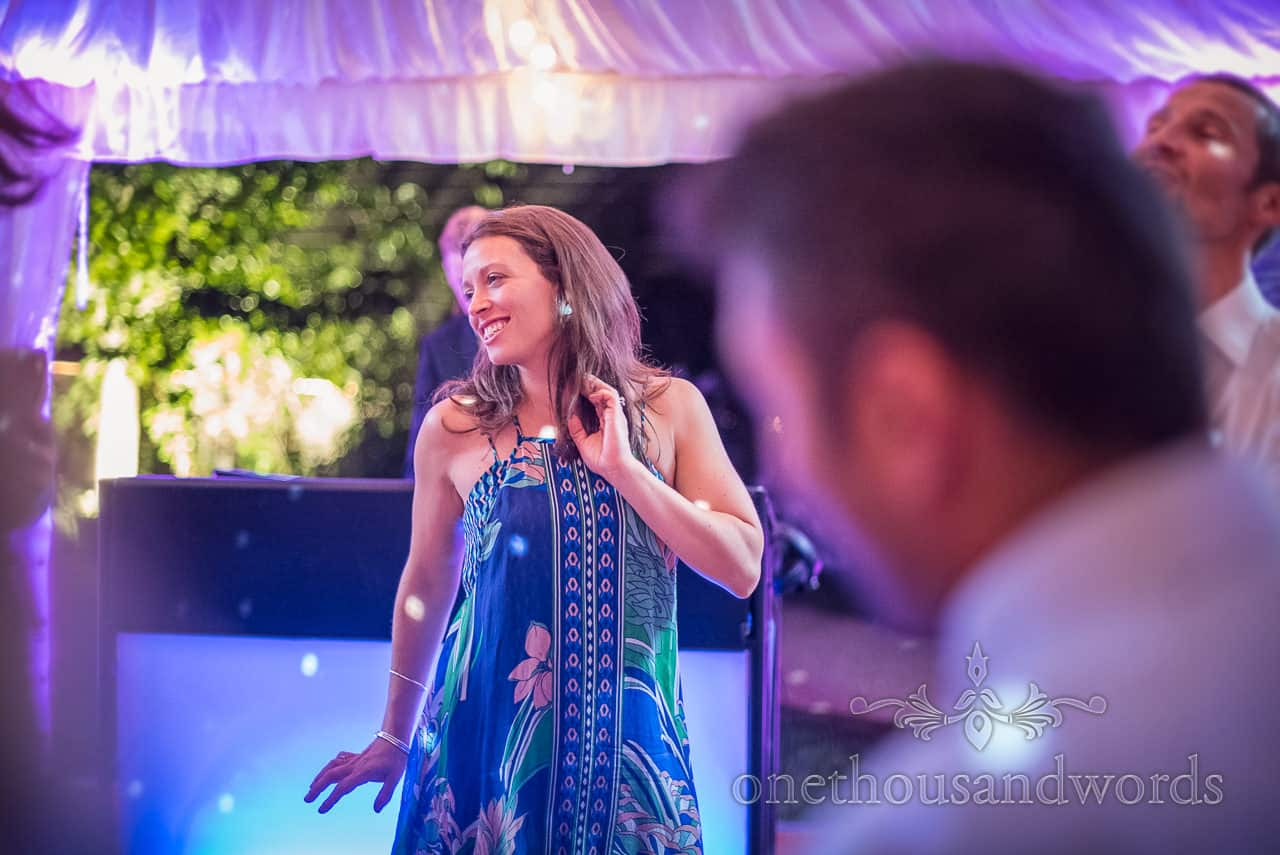 Smiling female wedding guest in blue patterned dress dancing under disco lights at Sherborne Castle wedding evening