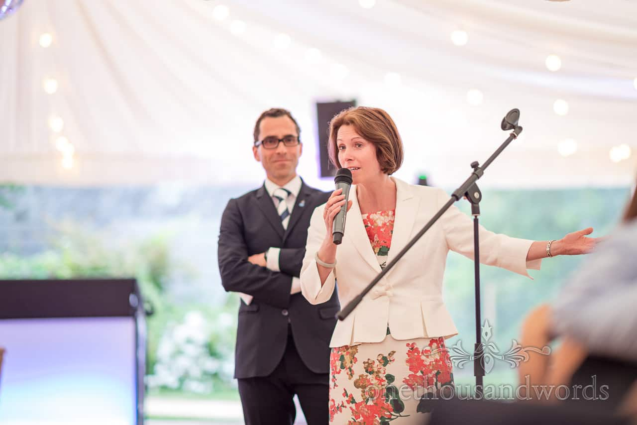 Animated female wedding guest in white suit jacket and floral print dress translates wedding speech into French