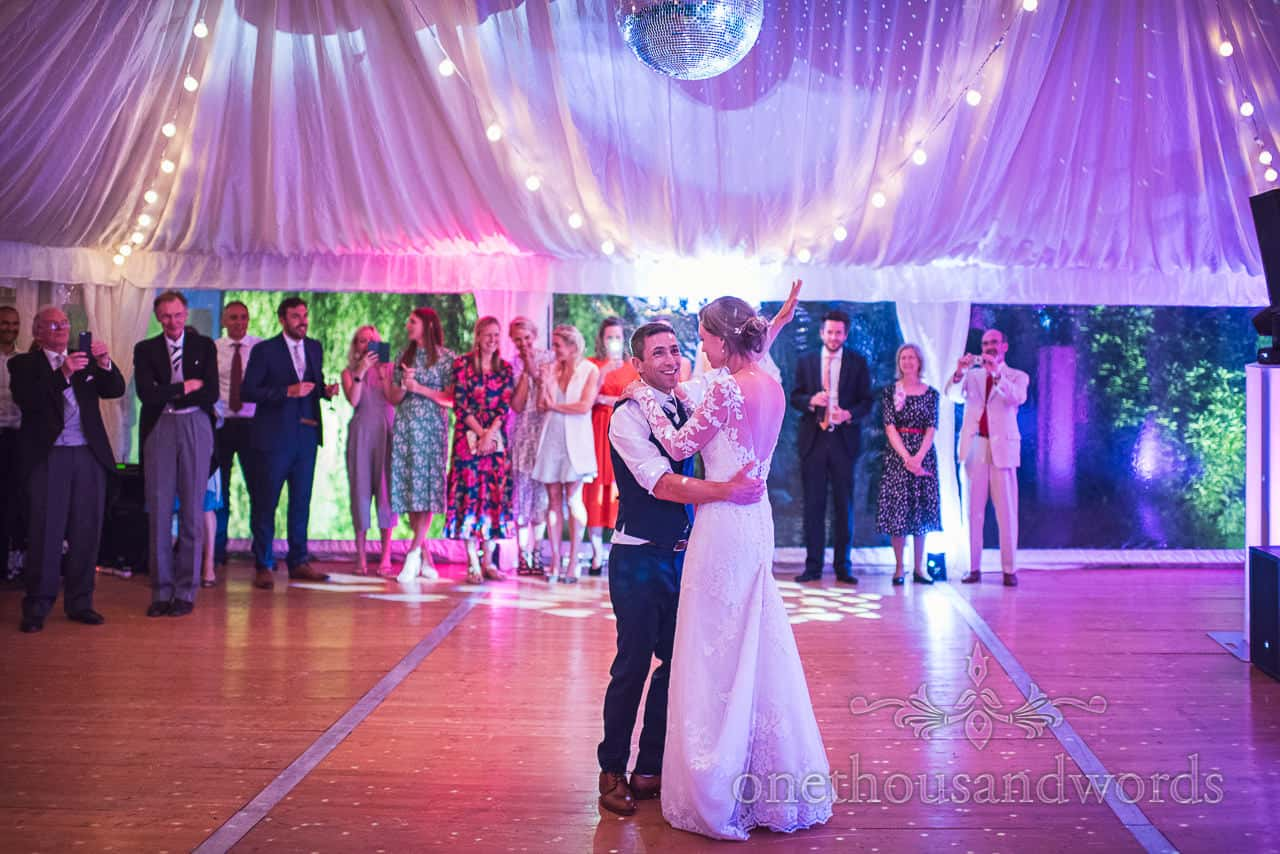 First dance at Sherborne Castle under disco lighting in wedding marquee is watched by wedding guests