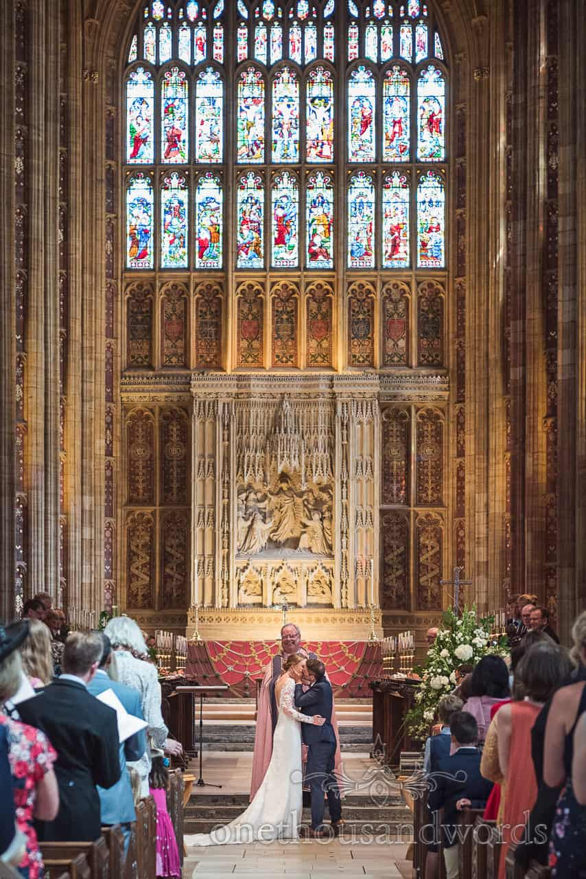 Bride and groom have first kiss under stained glass window at Sherborne Abbey wedding ceremony in Dorset