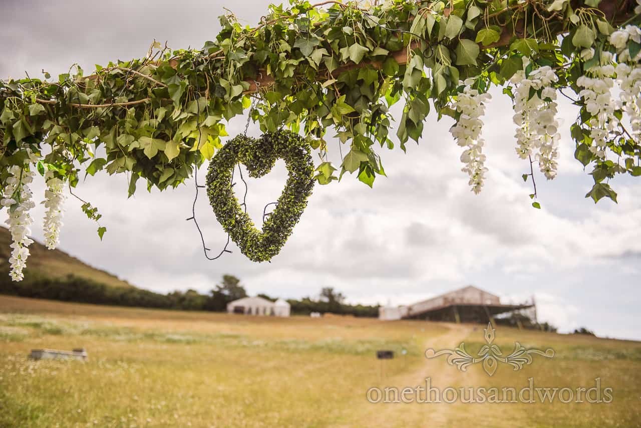 Floral archway with green foliage and love heart at entrance to footpath leading to wedding marquee field hill