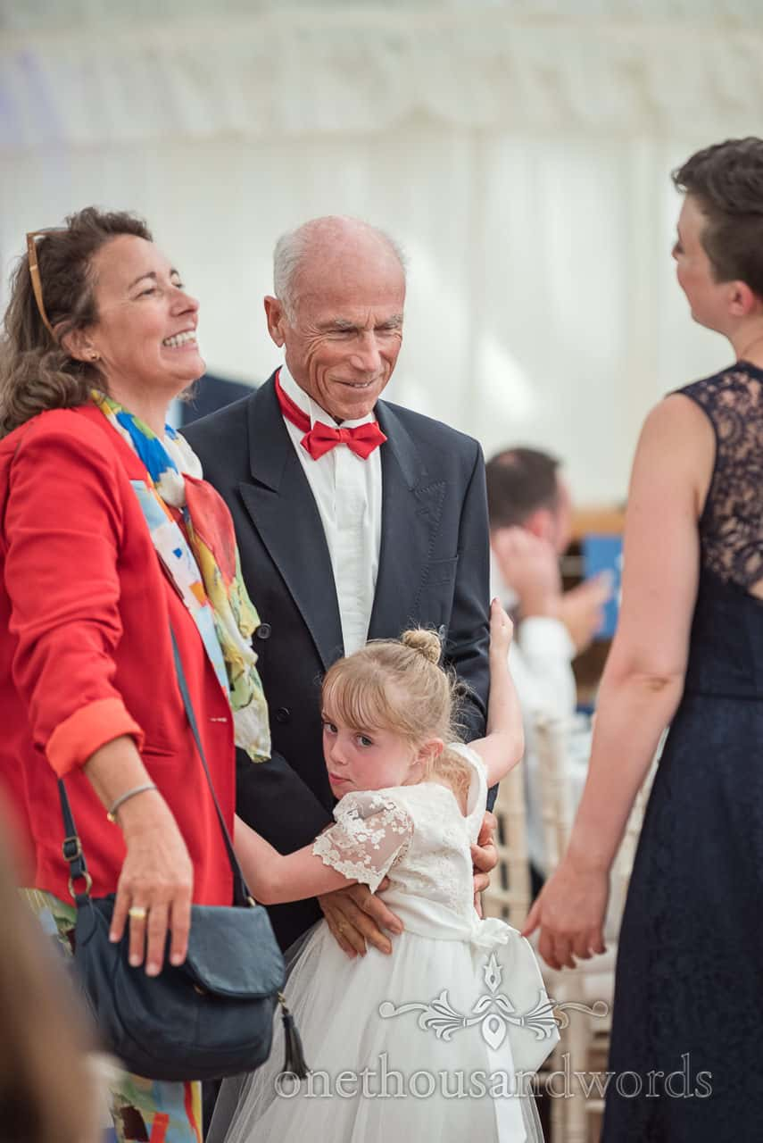 Flower girl in white dress hugs her grandfather with red bow tie and black suit at marquee wedding reception