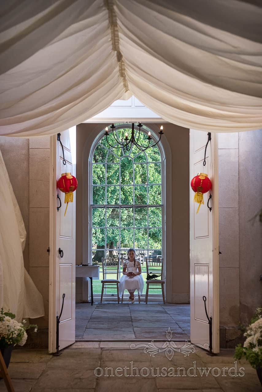 Flower girl sits in orangery window through doorway with marquee tunnel at Sherborne Castle wedding
