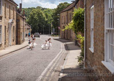 Flower girls in white dresses run across road on way to brides family home in Sherborne, Dorset