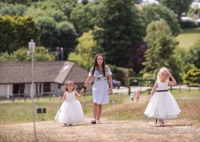 Flower girls are walked up grass hill towards wedding reception venue