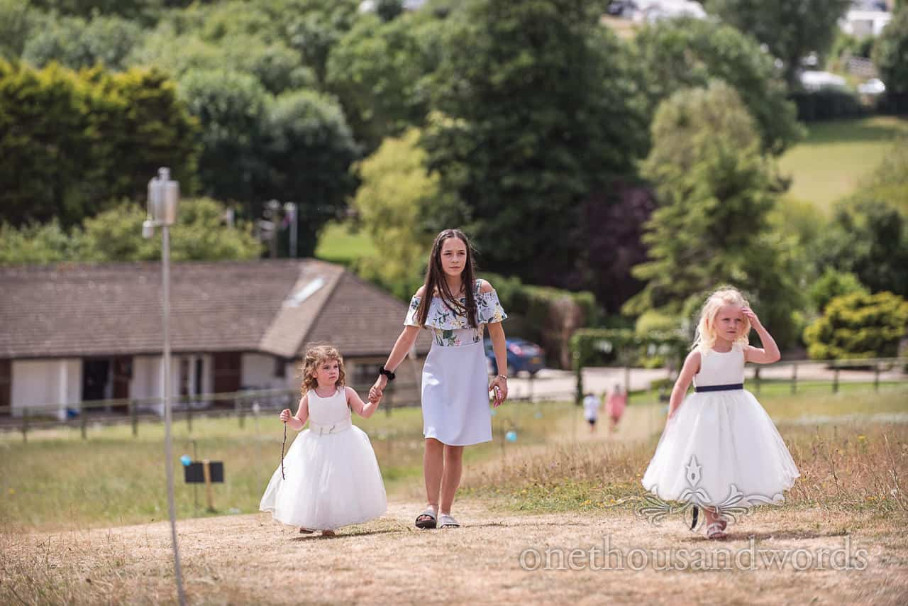 Flower girls are walked up grass hill towards wedding reception venue